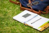 Nowoczesny cyfrowy notatnik rezygnować zdejmowany smartphone na zielonej trawie — Zdjęcie stockowe