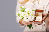 Close up of bride with bouquet of flowers and wedding ring. — Stock Photo