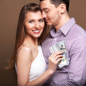 Fashion beautiful couple in love holding money the family budget — Stock Photo