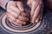 Hands working on pottery wheel — Stock Photo
