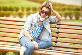 Fashion man sitting on a bench and listening to music — Stockfoto