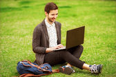 Young fashion male student sitting on grass in park and holding — Stock Photo