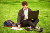 Young fashion male student sitting on grass in park and holding  — Stockfoto