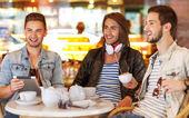 Mladí bederní kluci sedí v kavárně, chatování a pít kafe — Stock fotografie