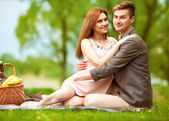 Couple in love in sitting near the river, picnic — Foto Stock