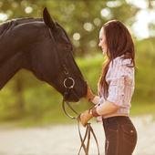 Ung kvinna med en häst i parken nära floden — Stockfoto