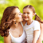 Mother and daughter hugging in love playing in the park — Stock Photo
