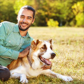 Man and central Asian shepherd walk in the park. — Stock Photo