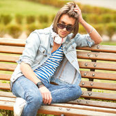 Fashion man sitting on a bench and listening to music — Stock Photo
