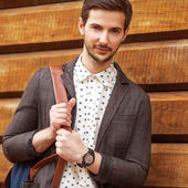 Portrait of young beautiful fashionable man against wooden wall. — Stock Photo