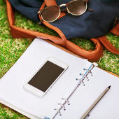Modern digital notebook with mobile smartphone on green grass — Zdjęcie stockowe