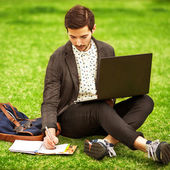 Young fashion male student sitting on grass in park — Foto Stock