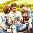 Three young men friends using tablet computer in park — Stock Photo #48836925