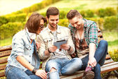 Three young men friends using tablet computer in park — Stock Photo
