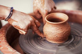 Hands working on pottery wheel , retro style toned — Stockfoto