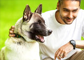 Man and Akita Inu dog  walk in the park. He keeps the dog on the — Stock Photo