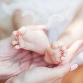 Novorozence baby nohy na ženských rukou — Stock fotografie