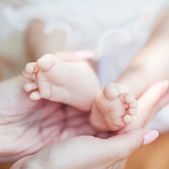 女性の手で生まれたばかりの赤ちゃんの足 — ストック写真