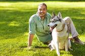 男とハスキー犬公園を歩く. — ストック写真