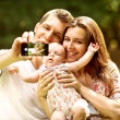 Family with baby In Park  taking selfie by mobile phone — Photo #51262807