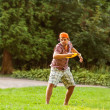 Man playing in the park with a plate frisbee — Stock Photo