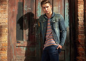 Tipo de estilo hipster. hombre de moda de pie cerca de una puerta de madera — Foto de Stock