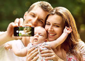 Family with baby In Park  taking selfie by mobile phone — Stock Photo