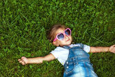 Little girl lying on the grass in sunglasses, fashion style — Stock fotografie
