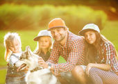 Dad and his two daughters in park with dog Husky spend fun time. — Stock Photo