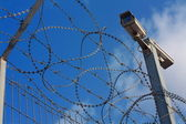 Barbed wire and surveillance camera — Stock Photo