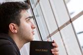 Hombre que sostiene la biblia mirando por la ventana — Foto de Stock