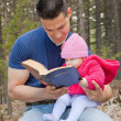Dad and Baby Daughter Reading Bible - Stock Photo