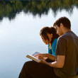 Couple Reading The Bible By A Lake — Stock Photo