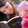 Mom And Baby Daughter Reading Bible - Stock Photo