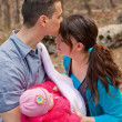 Dad Kissing Mom and Holding Baby — Stock Photo #25015977