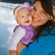 Stock Photo: Mom And Baby Daughter Smiling By A Lake