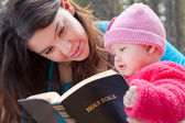 Mom And Baby Daughter Reading Bible — Stock Photo