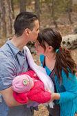Papá besando a mamá y bebé holding — Foto de Stock