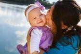Mamá besando a hija por lago — Foto de Stock