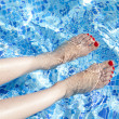 Sexy women legs splashing in tropical swimming pool — Stock Photo #12542349