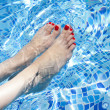 Stock Photo: Sexy women legs splashing in tropical swimming pool