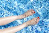Sexy vrouwen benen spetteren in tropisch zwembad — Stockfoto