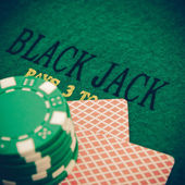 Vintage black jack table with red casino chips — Stock Photo