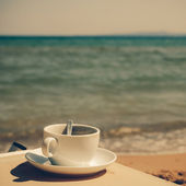 Cup of coffee at the beach - vintage coaster — Stock Photo