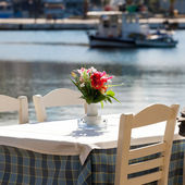 Greek beach with traditional blue table and chairs — Stock Photo