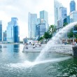 SINGAPORE-DEC 29: The Merlion fountain spouts water in front of the Singapore skyline — Stock Photo