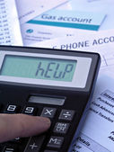 Bills and calculator displaying HELP — Stock Photo
