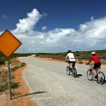ciclistas pasando un roadsign en blanco — Foto de Stock