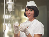 Nurse preparing to hold intravenous drip medication — Stock Photo
