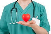 Doctor with red heart in hands — Stock Photo